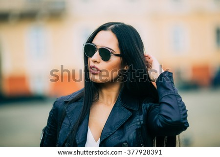 Young fashion brunette woman in sunglasses with jacket on city street - stock photo