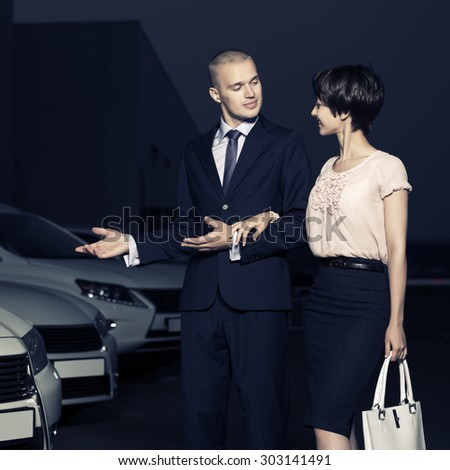 Young fashion business couple collecting new car at dealership lot - stock photo