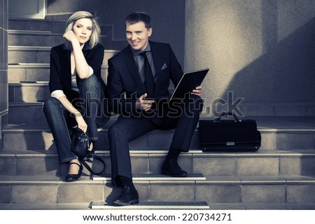 Young fashion business couple with laptop on the steps - stock photo