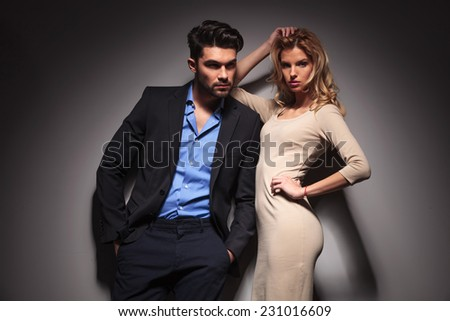 Young fashion business man looking away with his hands in pockets while his lover is leaning on him and fixing her hair. - stock photo