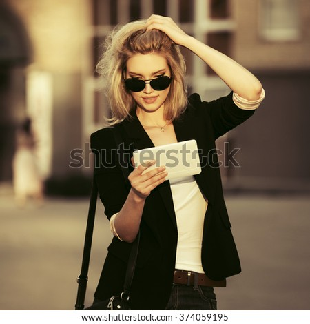 Young fashion business woman in sunglasses using tablet computer on city street - stock photo