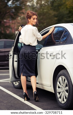 Young fashion business woman standing beside her car - stock photo