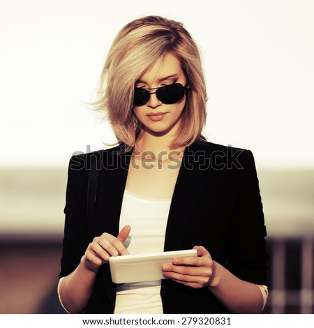 Young fashion business woman using tablet computer outdoor - stock photo