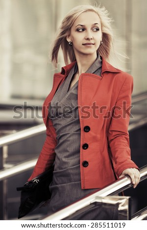 Young fashion business woman with handbag on the steps against office windows - stock photo