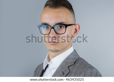 young fashion businessman with nerd glasses and stylish hairdo in jacket on studio background