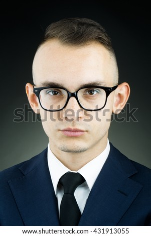 young fashion businessman with nerd glasses and stylish hairdo in jacket with tie on studio background closeup - stock photo