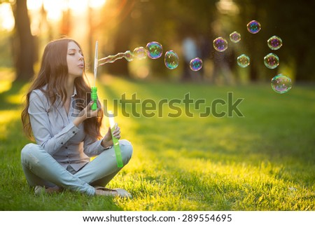 Young fashion casual woman blow bubbles in sunset in park Springtime Summertime Trendy girl sitting on  grass in  sunset Spring landscape background.  Sun rays Summer scene Sunlight background Backlit - stock photo