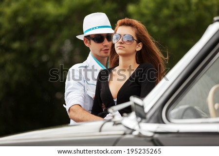 Young fashion couple at the classic car  - stock photo