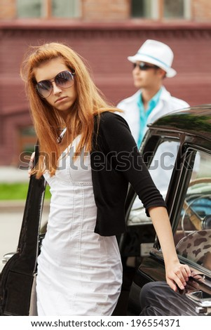 Young fashion couple in conflict at the retro car  - stock photo