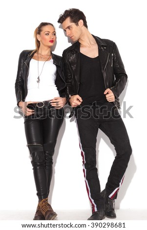 young fashion couple in leather clothes looking at each other, full body picture, leaning on a white wall