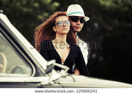 Young fashion couple in love at the classic car outdoor - stock photo