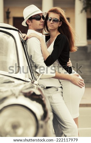 Young fashion couple in love at the retro car  - stock photo