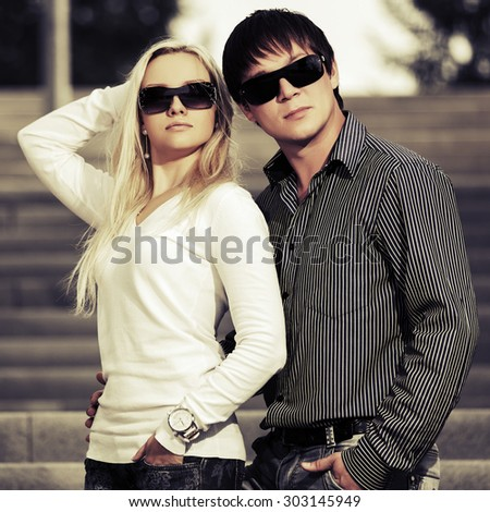 Young fashion couple in love on the steps - stock photo