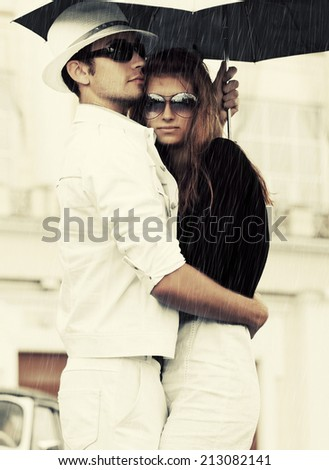 Young fashion couple in love with umbrella  - stock photo