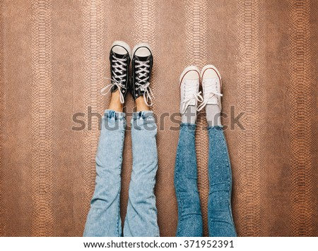 Young fashion couple's legs in jeans and sneakers feet up on wall - stock photo