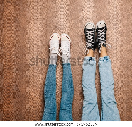 Young fashion couple's legs in jeans and sneakers feet up on wall. Close up - stock photo