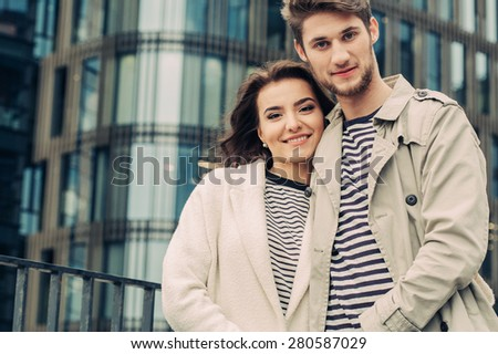 Young fashion couple walking down the street in summer near skyscraper. Pretty beautiful woman in stripes  clothes. Close-up portrait - stock photo