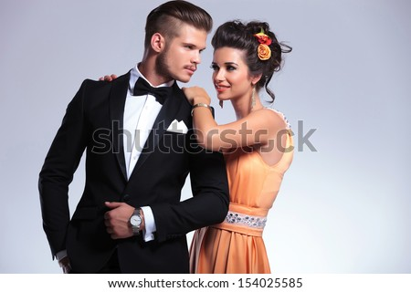 young fashion couple with woman behind man resting her hands on his shoulders while looking at him. on gray background - stock photo