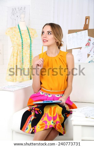 Young fashion designer draws new sketches collection - stock photo