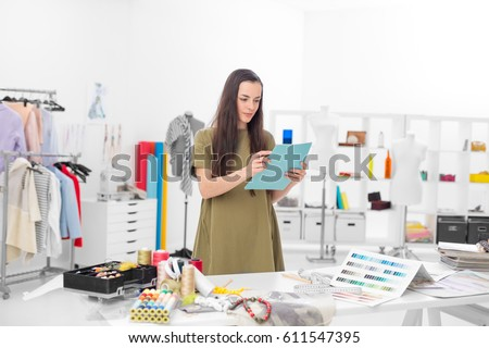 young fashion designer in her workshop looking confident at the ordering list