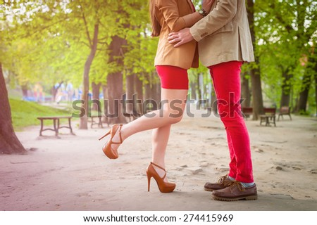Young fashion elegant stylish couple  feet , in love , stand opposite each other on park in spring sunny weather - stock photo