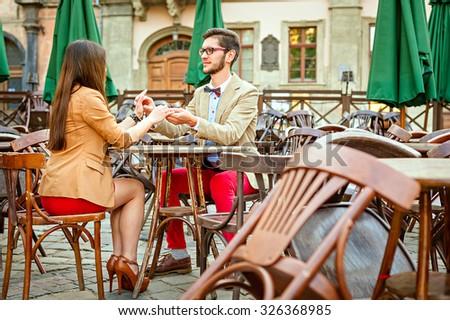 Young fashion elegant stylish couple posing on cafe of european city in summer - stock photo