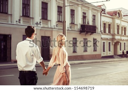 Young fashion elegant stylish couple posing on streets of european city in summer evening weather. Sensual blonde vogue girl with handsome hipster man walk on the road in europe - stock photo