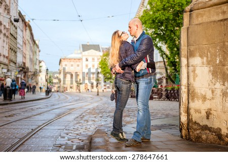 Young fashion elegant stylish couple stand opposite each other  and kiss, on streets of european city in summer morning - stock photo