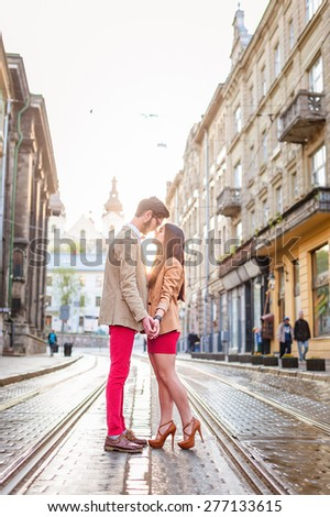 Young fashion elegant stylish couple stand opposite each other on streets of european city in summer morning, in Lviv city, Ukraine - stock photo