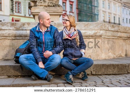 Young fashion elegant stylish couple, travel by old European cities, sitting on an old stone, with a backpack, on the square with paving stones - stock photo