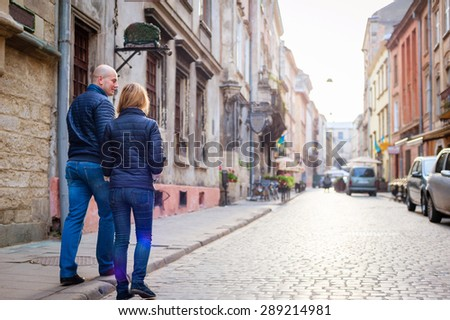 Young fashion elegant stylish couple walk  on streets of european city in summer morning - stock photo
