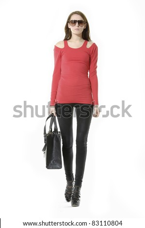 young fashion female in sunglasses with handbag. walking in Studio - stock photo