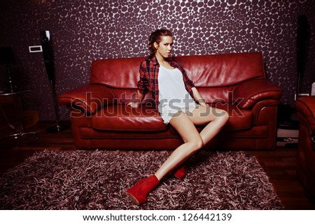young fashion girl in modern living room sit on leather sofa