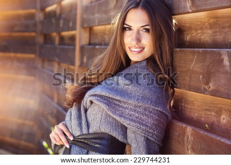 Young fashion girl near wooden wall - stock photo