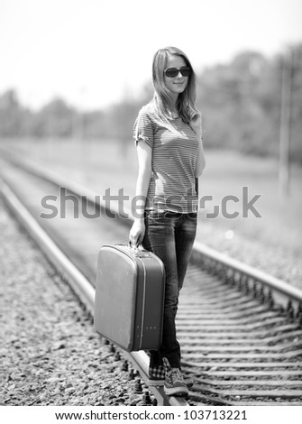 Young fashion girl with suitcase at railways. Photo in black and white style.