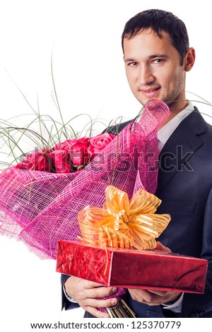 Young fashion handsome man with flowers and gift - stock photo