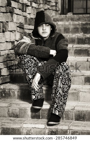 Young fashion hippie man sitting on the steps - stock photo