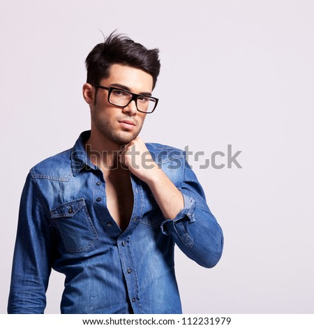 young fashion male model holding his collar and looking to the camera on gray background