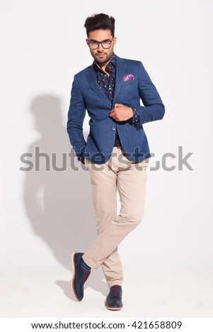 young fashion male model in suit holding button and posing in studio - stock photo