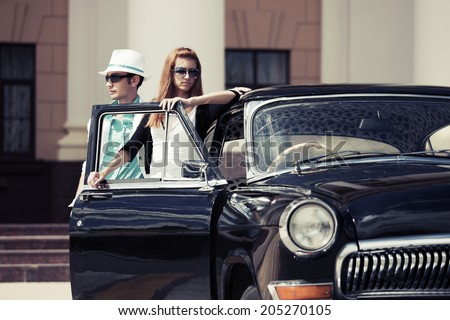 Young fashion man and woman at the retro car  - stock photo