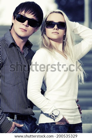 Young fashion man and woman on the steps  - stock photo