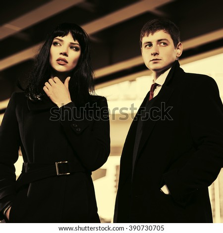 Young fashion man and woman walking on city street - stock photo