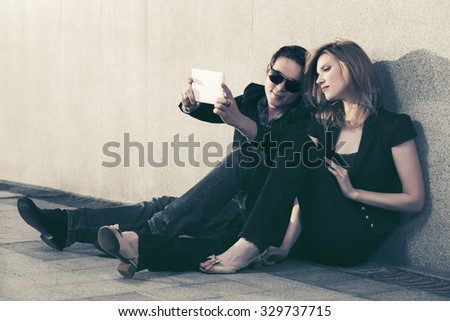 Young fashion man and woman with tablet computer sitting at the wall