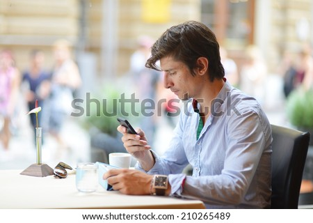Young fashion man / hipster drinking espresso coffee in the city cafe during lunch time and working on tablet computer - stock photo