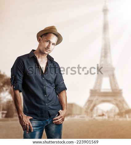 Young fashion man in dark blue shirt and jeans posing in paris, france - stock photo