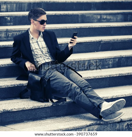 Young fashion man in sunglasses calling on mobile phone on the steps - stock photo