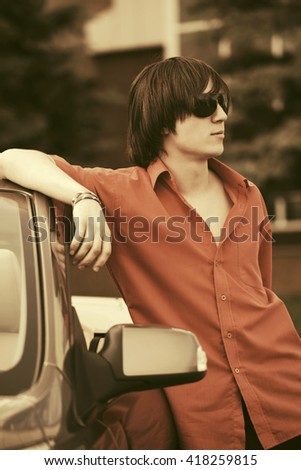 Young fashion man in sunglasses leaning on his convertible car. Male stylish model outdoor - stock photo