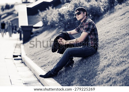 Young fashion man in sunglasses sitting on the grass in a city park - stock photo