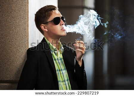 Young fashion man in sunglasses smoking a cigarette - stock photo