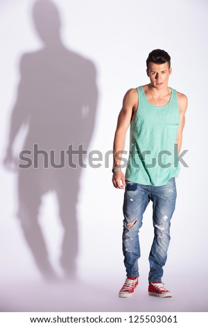 young fashion man looking at the camera and standing on white background with hard shadow - stock photo